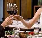 Young couple toasting with wine in restaurant