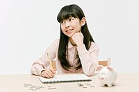 Girl sitting at desk with piggy bank