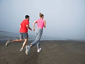 Couple jogging on foggy beach