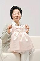 Senior woman holding baby dress