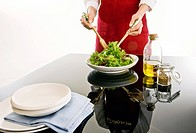 Young woman tossing salad at table