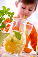 Jug of lemonade, girl drinking lemonade in background