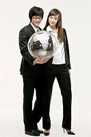 Businessman and businesswoman holding globe