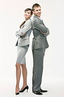 Businesswoman and man standing with backs together