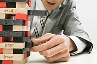 Businessman hand removing block from tower of blocks