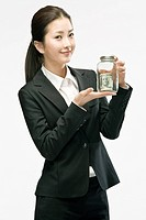 Busiensswoman holding money bottle, smiling