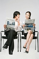 Business couple reading newspaper, sitting on chair
