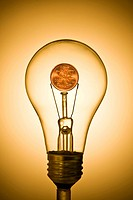 Close_up of lighting bulb with coin