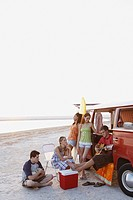 Friends lounging around van on beach
