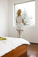 Woman staring out bedroom window (thumbnail)