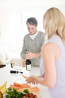 Man opening bottle of wine and woman preparing food in kitchen