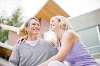 Couple hugging and laughing on deck of modern house