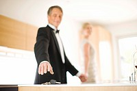 Couple in eveningwear reaching for keys on kitchen counter