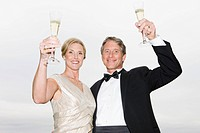 Portrait of couple in eveningwear holding champagne flutes (thumbnail)