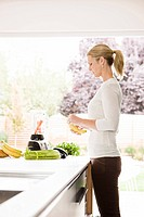 Woman preparing health shake in kitchen