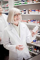 Pharmacist holding prescription bottle