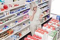 Woman reading label on bottle in drug store