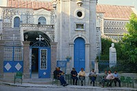 Men sitting outside decorated church in the old mastic village of Pyrgi, Chios, North Aegean Islands, Greek Islands, Greece, Europe