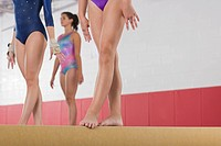 Gymnasts standing on a balance beam