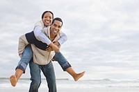 Man giving woman piggyback by the sea (thumbnail)