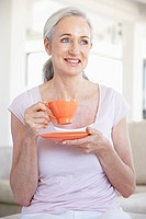 Senior Woman Holding Tea And Smiling At The Camera