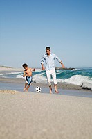 Father and son playing football by the sea