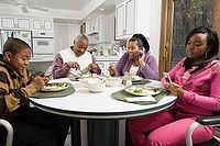 Family using cell phones at the dinner table
