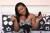 Teenage girl applying make up in bedroom