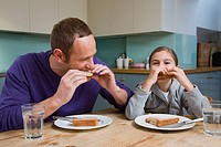 Father and daughter eating sandwiches