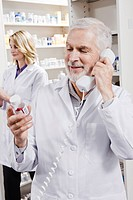 Pharmacist holding pill bottle and talking on telephone (thumbnail)