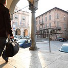 Businessman checks watch heads into historic town center Moncalieri Turin area