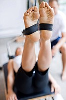 Close up of womanís feet in straps of pilates equipment