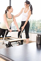 Personal trainer guiding woman on pilates equipment
