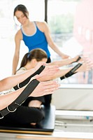 Personal trainer guiding women on pilates equipment