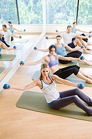 People working out with weight balls on mats in exercise class