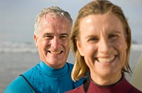 Couple wearing wetsuits on a beach