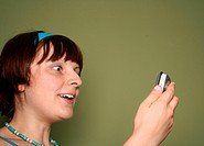 young woman calling by cellular phone over green