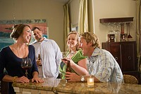 Four Caucasian friends sitting with drinks in kitchen, laughing