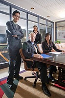 Portrait of four multi_ethnic businesspeople in boardroom, smiling