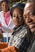 Close up of African American father with children outdoors in park, looking at camera