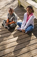 Portrait of young African American boy and girl outdoors sitting on boardwalk, looking at camera