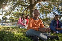 Portrait of young African American family sitting in park, looking at camera