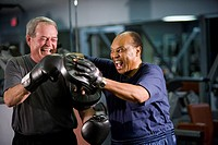 Multi_ethnic senior men laughing and boxing at gym