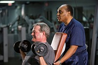 Portrait of multi_ethnic senior men lifting hand weights at gym