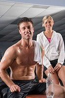Portrait of young woman standing and young man sitting on weight bench in gym