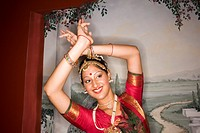 Portrait of Indian woman dancing in traditional dress in front of mural, holding a pose