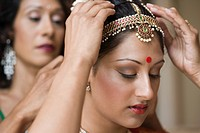 Mother putting hairpiece on young Indian woman in traditional dress, focus on foreground
