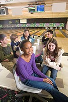 Portrait of multi_ethnic teenagers sitting around table in bowling alley