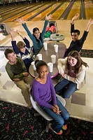 Portrait of multi_ethnic teenagers sitting around table in bowling alley with arms raised, high angle view
