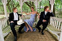 Young men in western suits and young blonde woman in evening gown sitting inside gazebo